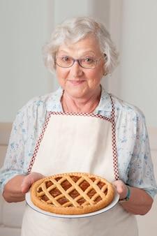 Szczęśliwa uśmiechnięta starsza kobieta pokazuje jej morelową tartę