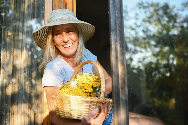 Szczęśliwa uśmiechnięta starsza kobieta pozuje przez otwarte okno w starym drewnianym wiejskim domu w słomkowym kapeluszu z koszem kwiatów.