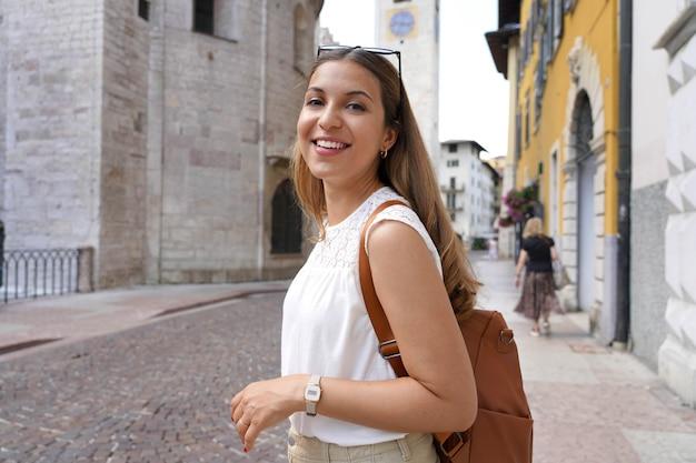 Szczęśliwa uśmiechnięta turystka odwiedzająca stare średniowieczne miasto trento, włochy