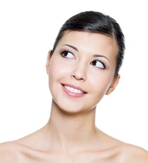 Szczęśliwa uśmiechnięta twarz młodej dorosłej kobiety patrząc w górę -