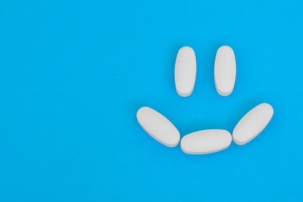 Szczęśliwa uśmiechnięta twarz ułożona z białych tabletek medycznych. apteka, witamina, koncepcja tabletek.