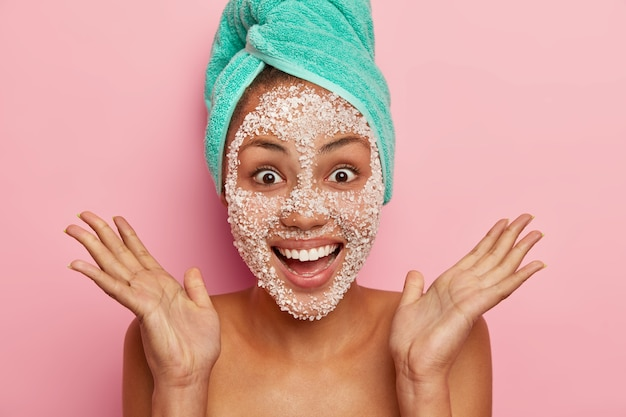 Szczęśliwa, uszczęśliwiona kobieta rozkłada dłonie w pobliżu twarzy, ma zębaty uśmiech ma białą maskę z soli morskiej, nosi owinięty turkusowy ręcznik, stoi bez koszuli na różowej ścianie