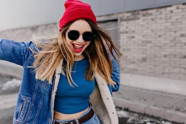 Szczęśliwa uwodzicielska dziewczyna w dżinsach z brązowym paskiem, zabawy na ulicy. zewnątrz portret spektakularnej kobiety rasy kaukaskiej w czarnych okularach przeciwsłonecznych tańczących na murze miejskim.