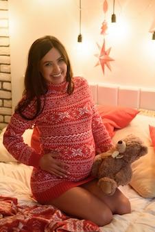 Szczęśliwa w ciąży na łóżku