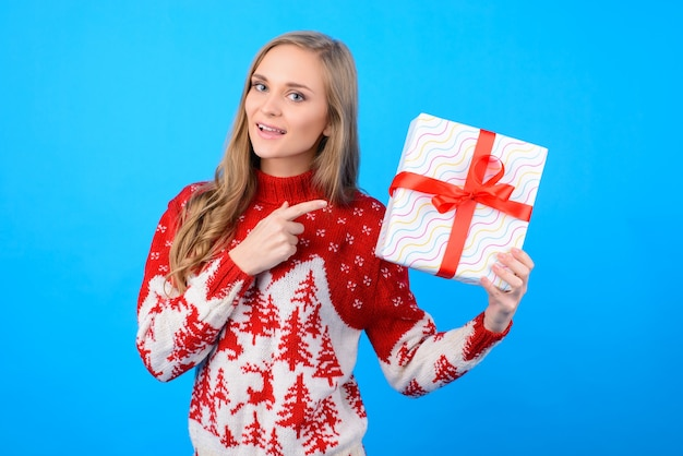 Szczęśliwa w przedświątecznym nastroju pani wybiera prezent na ferie zimowe. wskazuje na pudełku, które trzyma w dłoni.
