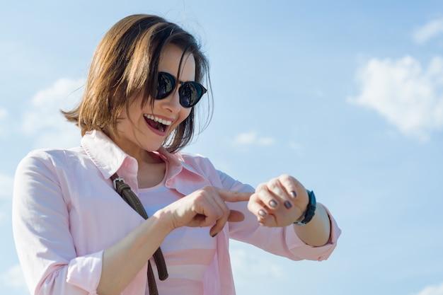 Szczęśliwa w średnim wieku biznesowa kobieta patrzeje zegar.