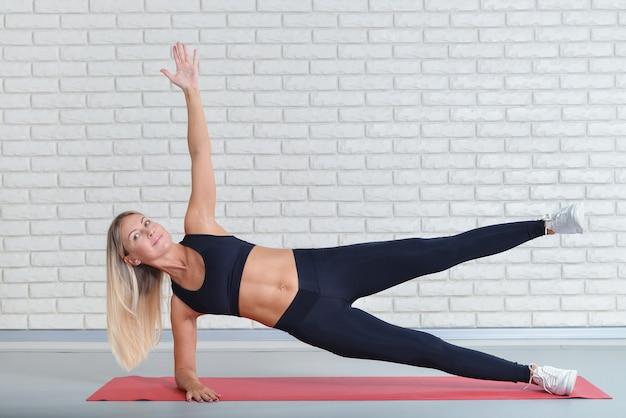 Szczęśliwa w średnim wieku kobieta ćwiczy na joga macie, sprawność fizyczna trening przy gym