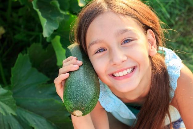 Szczęśliwa wegańska dziewczyna z świeżą zieloną cukinią w ogrodzie kuchennym na zewnątrz