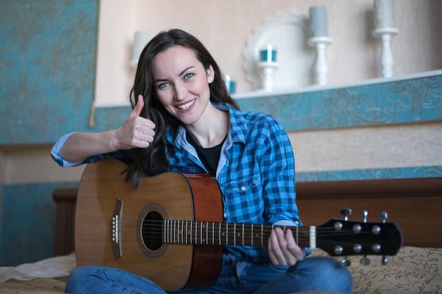 Szczęśliwa wesoła brunetka siedzi na łóżku z gitarą akustyczną i pokazuje kciuk do góry