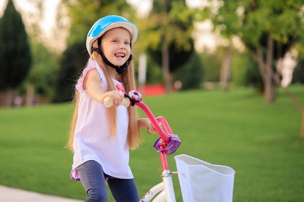 Szczęśliwa wesoła dziewczyna dziecko na rowerze w parku