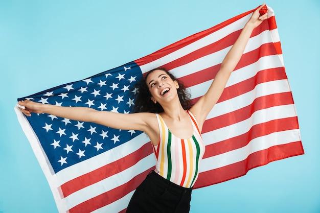 Szczęśliwa wesoła dziewczyna niosąca amerykańską flagę, stojąc na białym tle
