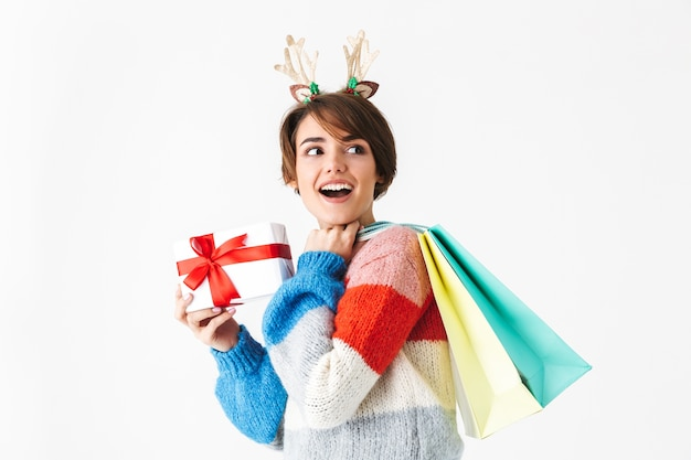Szczęśliwa wesoła dziewczyna ubrana w sweter stojący na białym tle na białym, trzymając obecne pudełko, niosąc torby na zakupy