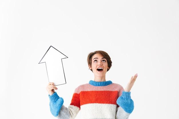 Szczęśliwa wesoła dziewczyna ubrana w sweter stojący na białym tle, skierowana w górę strzałką papieru