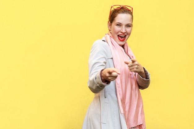 Szczęśliwa wesoła dziewczyna z piegami, na sobie płaszcz, różowy szalik, czerwone okulary, patrząc i wskazując palcem na aparat. studio strzał, żółte tło