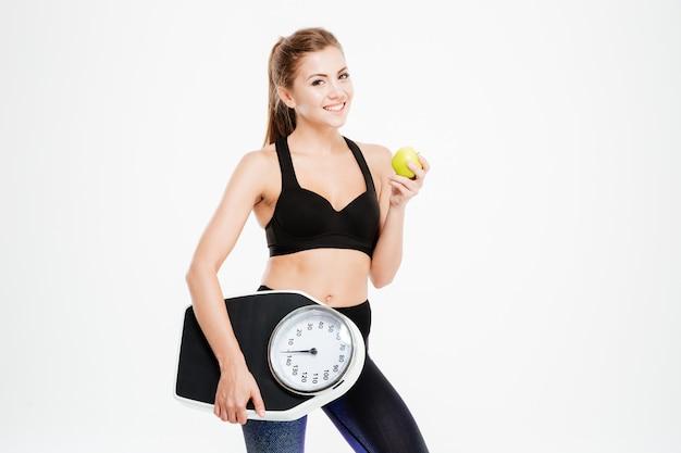 Szczęśliwa wesoła kobieta fitness trzyma wagę i zielone jabłko na białym tle