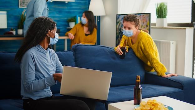 Szczęśliwa wesoła kobieta trzymająca butelkę piwa patrząca na laptopa rozmawiająca z afrykańskim przyjacielem w salonie nosząca maskę na twarz, aby zapobiec rozprzestrzenianiu się koronawirusa w czasie globalnej pandemii. materiał koncepcyjny.