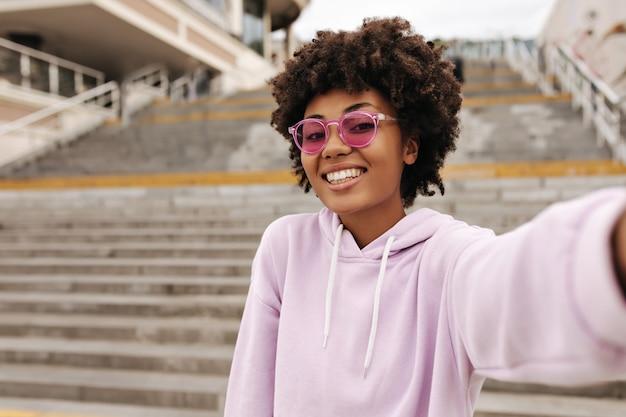 Szczęśliwa, wesoła, kręcona kobieta w fioletowej oversize'owej bluzie z kapturem i różowych okularach przeciwsłonecznych uśmiecha się i robi selfie na zewnątrz w pobliżu schodów