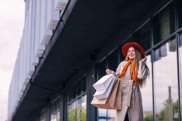 Szczęśliwa wesoła młoda kobieta na sobie płaszcz z torby na zakupy