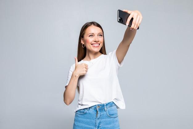 Szczęśliwa wesoła młoda kobieta pokazuje kciuk i robi selfie na smartfonie na białym tle