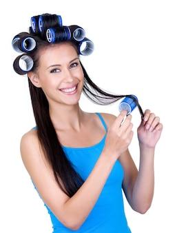 Szczęśliwa wesoła młoda kobieta robi piękną fryzurę z hairrollers - na białym tle
