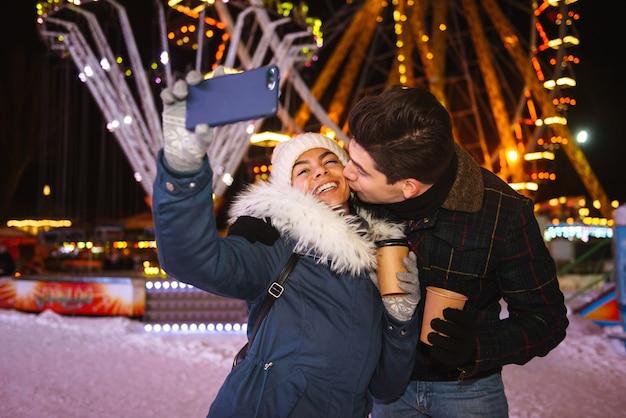 Szczęśliwa wesoła młoda para zabawy na łyżwach w nocy, trzymając filiżanki kawy na wynos, biorąc selfie