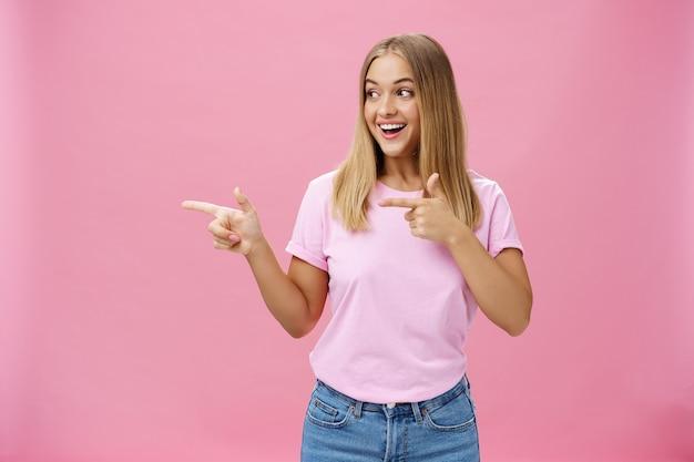 Szczęśliwa wesoła młoda pulchna dziewczyna z jasnymi włosami, wskazując i patrząc w lewo na różowym tle, wyrażając pozytywne emocje.