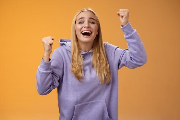 Szczęśliwa wesoła młoda wspierająca kobieta kibicująca siostrze wygrywająca uśmiechnięta, oddana zabawa nadzieja ulubiona drużyna zdobywająca bramkę wznoszenie zaciśniętych pięści wrzeszcząca radośnie świętująca triumfalne zwycięstwo, pomarańczowe tło.