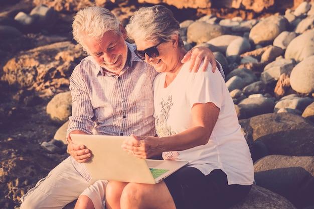 Szczęśliwa, wesoła, nowoczesna para starszych ludzi rasy kaukaskiej razem korzystających z laptopa technoogy na świeżym powietrzu z połączeniem internetowym