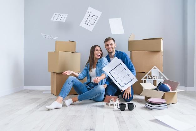 Szczęśliwa wesoła para zakochanych bawi się razem w swoim nowym mieszkaniu po wyjęciu z kartonów