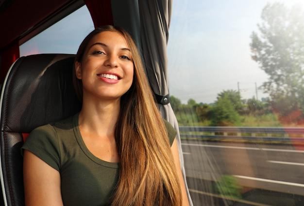 Szczęśliwa wesoła piękna podróżnik kobieta w autobusie patrząc na kamery.