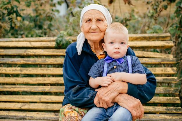 Szczęśliwa wesoła prababcia siedzi z wnukiem na zewnątrz