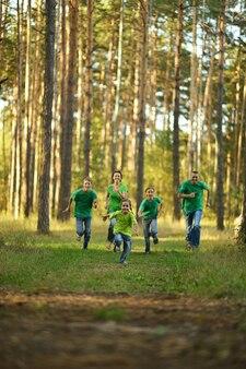Szczęśliwa wesoła rodzina biegająca w letnim parku