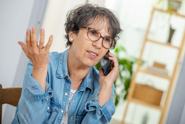 Szczęśliwa wiek średni kobieta z szkłami używać telefon i opowiadający