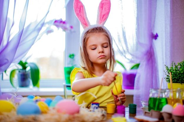 Szczęśliwa wielkanoc kobieta w królików ucho maluje jajka, małe dziecko w domu. ferie wiosenne