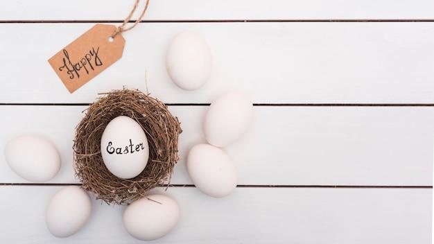 Szczęśliwa wielkanocna inskrypcja na jajku w gniazdeczku