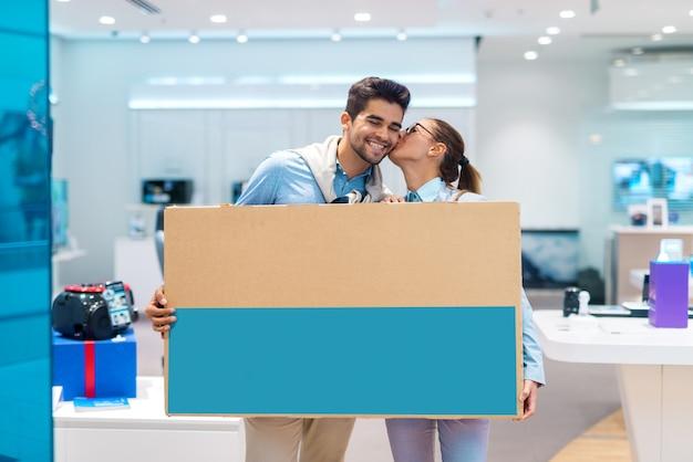 Szczęśliwa wielokulturowa para trzyma rozpakowaną telewizję podczas gdy stojący w technika sklepie.