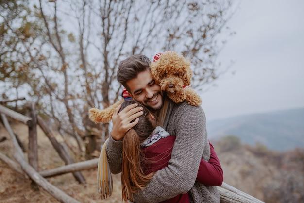 Szczęśliwa wielokulturowa para zakochanych ubrana na co dzień przytulanie w przyrodzie jesienią. mężczyzna mający psa na ramionach.