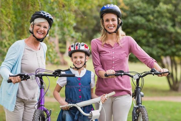 Szczęśliwa wielopokoleniowa rodzina na ich rowerze w parku