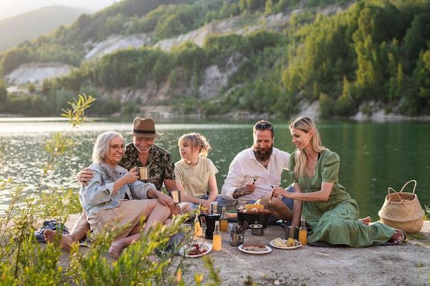 Szczęśliwa wielopokoleniowa rodzina na letnie wakacje, grill nad jeziorem.