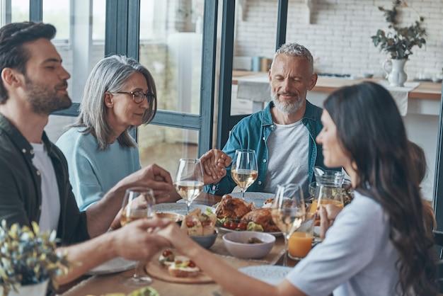 Szczęśliwa wielopokoleniowa rodzina trzymająca się za ręce i modląca się przed obiadem