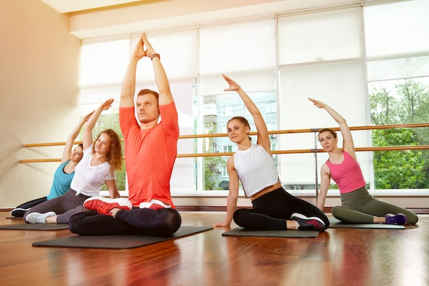 Szczęśliwa wielorasowa grupa młodych, uśmiechających się pięknych dziewczyn i szyb w odzieży sportowej, wykonująca ćwiczenia jogi w pozycji lotosu. zajęcia jogi lub fitness. grupowa koncepcja fitness, treningi grupowe, motywacja.