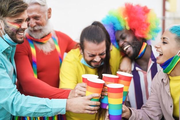 Szczęśliwa wielorasowa grupa przyjaciół bawiąca się na imprezie dumy lgbt