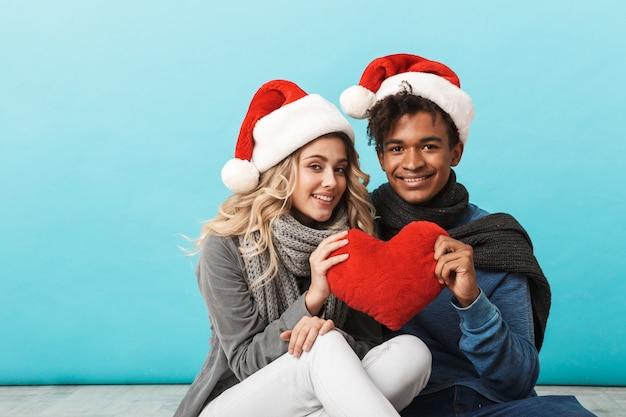 Szczęśliwa wielorasowe młoda para ubrana w boże narodzenie czerwone kapelusze odizolowane na niebieskiej ścianie, siedząc, trzymając czerwone serce