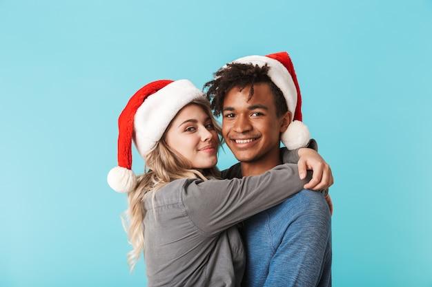 Szczęśliwa wielorasowe młoda para ubrana w czerwony kapelusz boże narodzenie na białym tle nad niebieską ścianą, przytulanie