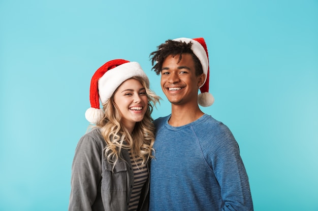 Szczęśliwa wielorasowe młoda para ubrana w czerwony kapelusz boże narodzenie na białym tle nad niebieską ścianą