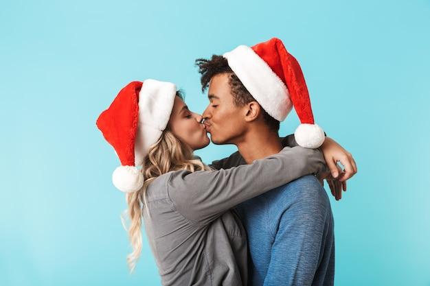 Szczęśliwa wielorasowe młoda para ubrana w czerwony kapelusz boże narodzenie odizolowane na niebieskiej ścianie, całując