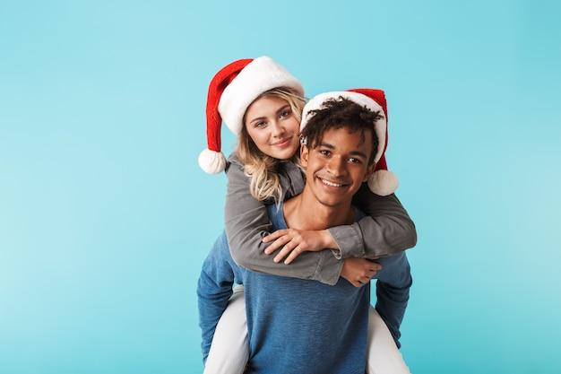 Szczęśliwa wielorasowe młoda para ubrana w czerwony kapelusz boże narodzenie odizolowane na niebieskiej ścianie, jazda na barana