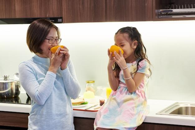 Szczęśliwa wietnamska mama i jej córeczka jedzą pyszne soczyste pomarańcze w kuchni na śniadanie