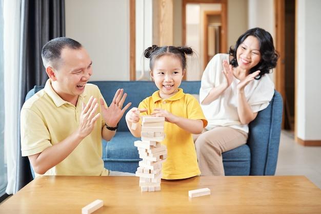 Szczęśliwa wietnamska mama i tata klaszczą córeczce kończąc wieżę z drewnianych klocków