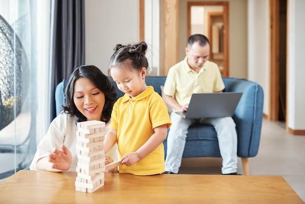 Szczęśliwa wietnamska matka i ojciec robi wieżę z drewnianych cegieł whe ojciec pracuje na laptopie w tle